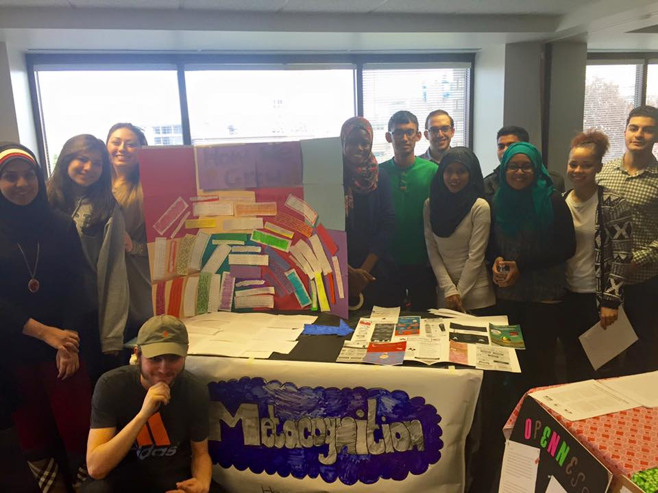A group of students is gathered around the poster and table display they made.